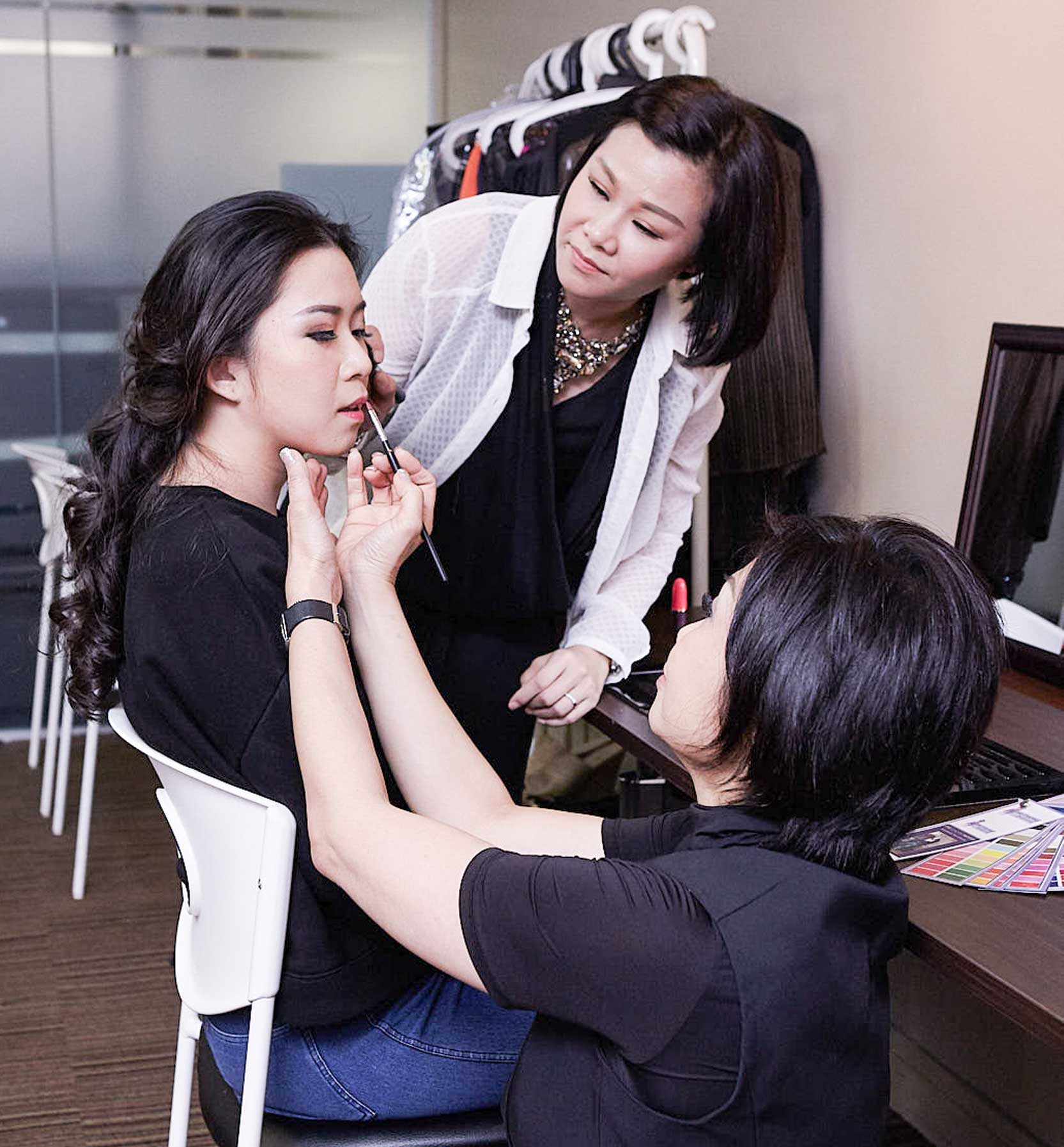 Photo of a student having her make applied by two style coaches from Singapore